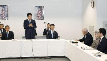 拉致被害者家族(右側)と面会し、あいさつする安倍首相(左から2人目)。左端は菅拉致相=16日午後、東京都千代田区