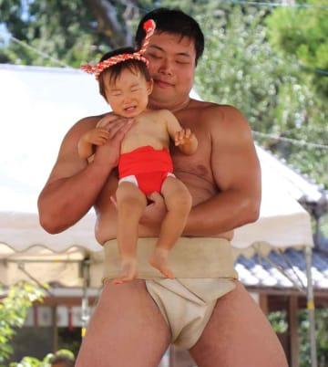 力士に抱えられて、土俵入りする赤ちゃん。大泣きする子を見ながら、保護者が健康を祈った(亀岡市篠町・篠八幡宮)