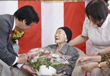 福岡県の小川洋知事(左)からお祝いの花を受け取る田中カ子さん=16日午後、福岡市