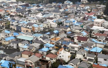 大規模停電を引き起こした台風15号の通過から1週間。千葉県鋸南町では多くの住宅の屋根にシートが掛けられ、作業する人の姿が見られた=16日午後