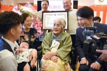 家族らに囲まれて笑顔の田中キクヱさん(中央)=南さつま市加世田小湊