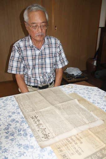 明治時代中期に発行された安芸津新報を見る荒田さん