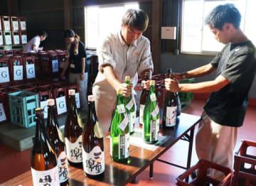 集まった日本酒を地域ごとに仕分ける学生や市職員