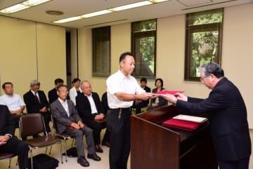 【中村委員長(右)から当選証書を受け取る新町議=玉城町役場で】