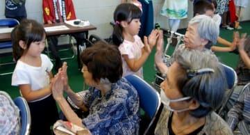 【園児と手遊びを楽しむ参加者ら=亀山関町泉ヶ丘の関文化交流センターで】