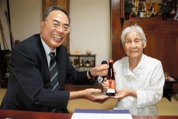 熊本善意銀行の井手輝利専務理事(左)から記念品を受け取った福原タツさん=人吉市