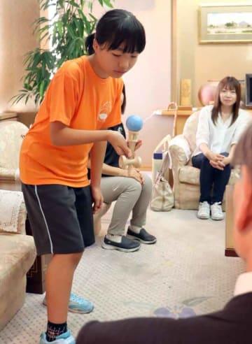 橋川市長らの前でけん玉を披露する加藤さん(滋賀県草津市役所)