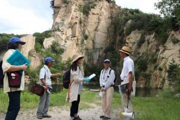 採石後にできた「丁場湖」で山田館長(右)の助言を聞く受講生=6日、北木島