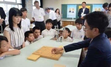 児童を前に模範対局する菅井七段(手前右)と村田女流二段(左から2人目)