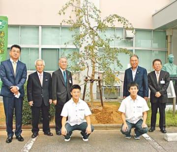 しだれ桜を植樹して記念写真に納まる学校関係者ら