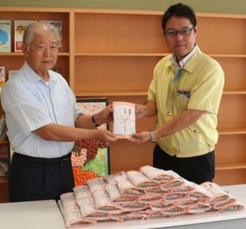 【中村次長(右)からさわ餅を受け取る田上会長=松阪市鎌田町で】