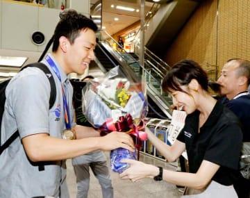 出迎えた今治市役所の同僚から花束を受け取る山口尚秀選手(左)=17日午後7時ごろ、松山空港