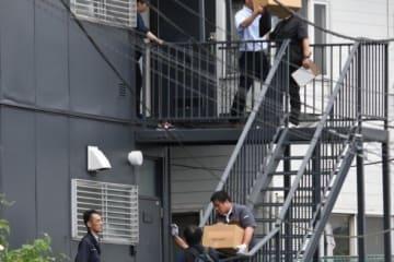 逃走した容疑者をかくまった容疑で逮捕された住人の男(38)の自宅アパートから押収品を運び出す神奈川県警の捜査員=6月23日午後6時15分ごろ、横須賀市