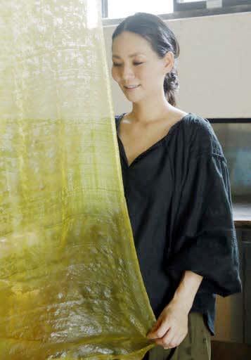刈安(かりやす)でグラデーションに染めた絹のストールを干す吉岡さん