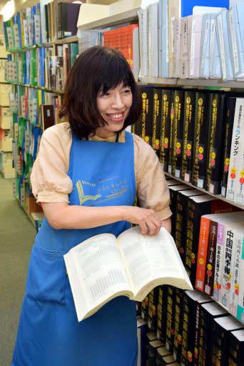 広島市立中央図書館のビジネス支援情報コーナーで資料を紹介する土井主事
