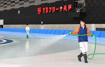 29日の供用開始に向け、整氷作業に励む担当者=18日、八戸市立屋内スケート場「YSアリーナ」