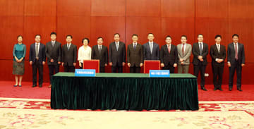 Yang Maorong (7th from L), head of Tianjin Binhai New Area, Tamotsu Matsui (8th from L), managing director of Meiji Dairies (Tianjin) Co., and Kiyoshi Nakao (9th from L), managing director of Meiji China Investment Co., and others pose for photos dur