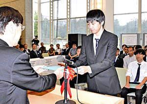 岡学長から学位記を受ける学生(右)