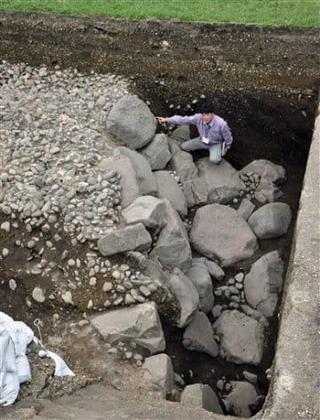 地中から発見された石垣について解説する野田班長=18日午後、三戸町梅内の城山公園