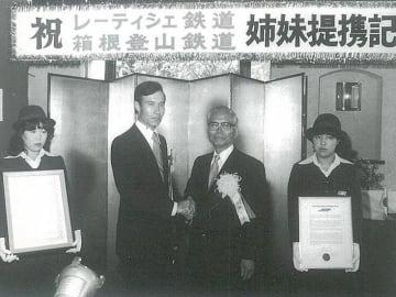 姉妹鉄道の締結式で握手する箱根登山鉄道の古瀬幸悦社長(右)とレーティッシュ鉄道のJ・ハッツ専務。当時は「レーティシェ」と表記していた =1979年(箱根登山鉄道提供)