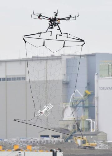 2016年1月、テロ対処訓練で小型のドローンを捕獲する警視庁の「迎撃ドローン」(上)=東京都江東区