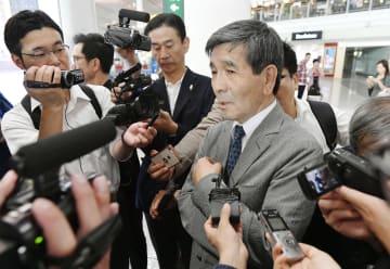 訪朝を終え、北京国際空港で記者団の取材に応じる金丸信吾氏=19日(共同)