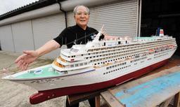 豪華客船「飛鳥2」の模型を完成させた藤原良長さん=香美町香住区香住