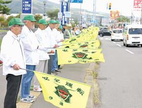 黄色い安全旗で交通事故防止を訴える参加者たち