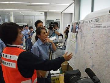 被害を示す地図を前に石井市長(左)から説明を受ける今井政務官(中央)=19日午前11時10分、君津市保健福祉センター