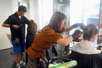 美容師の卵の研究生から、カットなどの施術を受ける客=19日、那覇市牧志の琉美インターナショナルビューティカレッジ