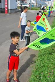 国道沿いで一生懸命旗を振る児童たち
