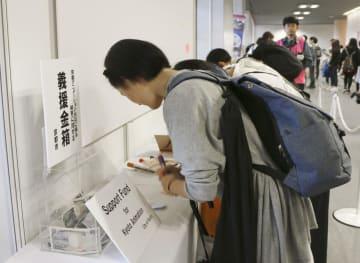 会場に設けられた京都アニメーションへの応援コーナーで、メッセージを書き込むファン=21日午前、京都市