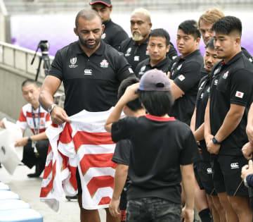小中学生との交流イベントでラグビー日本代表のジャージーをプレゼントするリーチ(左端)=21日、東京都内