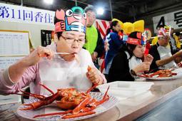 香住ガニにかぶりつく早食い大会の参加者たち=香住漁港西港