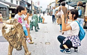 銅製の「銅物」にまたがって記念撮影する子どもたち