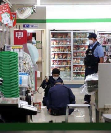 強盗があったコンビニエンスストアを調べる捜査員(21日午前5時13分)