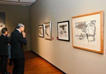 「会津の冬」を鑑賞する来場者。墨画と版画の違いを見比べることができる