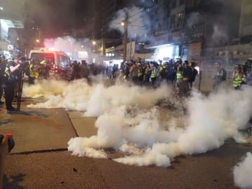 Police fire tear gas on Castle Peak Road in Yuen Long. Photo: Benjamin Yuen/United Social Press.