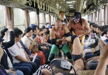山形鉄道フラワー長井線の車内で行われた「ローカル線プロレス2019」=22日