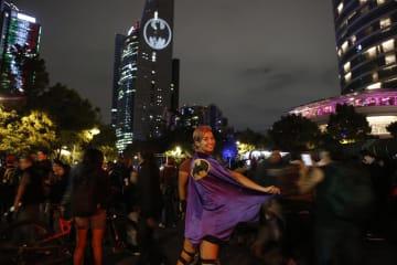 21日、メキシコ市でバットマンのマークがあるマントを着た女性(AP=共同)