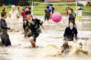 泥まみれになりながら懸命にプレーする選手=9月22日、福井県越前町大谷の陶寿園水田特設コート