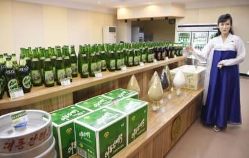 「大同江ビール」の工場に並ぶ製品。右は案内役の金潤姫さん=10日、平壌(共同)