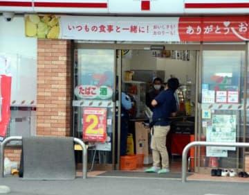 強盗事件が起きたコンビニの店内を調べる捜査員(23日午後3時19分)