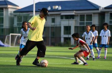 78歳のサッカーコーチ、フィールドで子どもたちを指導