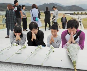献花台で震災犠牲者に手を合わせる親子。奥は東日本大震災津波伝承館と道の駅が入る建物