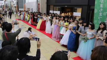 ファッションショーで自作の衣装を着て、レッドカーペット上に並ぶ大津高生たち(大津市長等2丁目)
