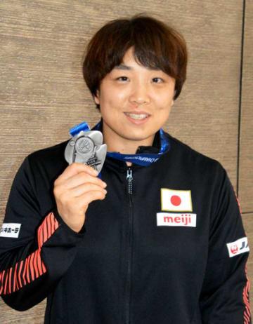 銀メダルを掲げ、笑顔を見せる皆川選手