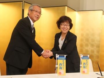 協定書に署名し博多大丸の香川社長(右)と握手する杉澤市長=西海市大島町、オリーブベイホテル