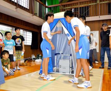 訓練で簡易トイレを組み立てる中学生ら▼