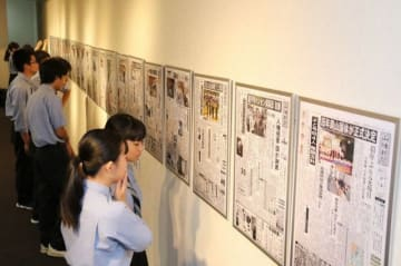 平成の大きなニュースを伝える紙面に見入る入場者